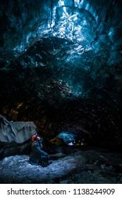 Female explorer crouching inside ice cave tunnel, Iceland