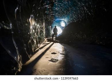 Female explorer inside ice cave tunnel