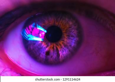 Female eye close up, with neon light. Black hole and lights in the eye. Two black dots in the eye