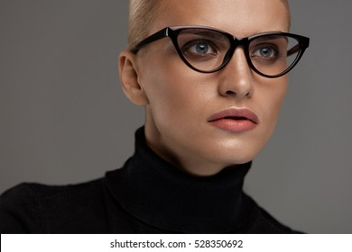 Female Eyeglasses. Portrait Of Beautiful Young Woman Wearing Black Eye Cat Design Glasses Frame, Fashion Eyewear. Attractive Blonde Girl In Stylish Optical Glasses On Grey Background. High Resolution