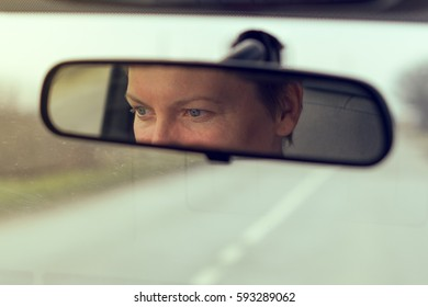Female eyes focusing on road, reflection in vehicle rearview mirror, retro toned image