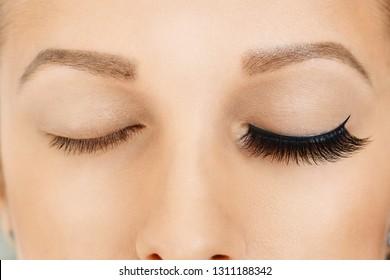 Female eyes with long false eyelashes, befor and after effect. Eyelash extensions, make-up, cosmetics, beauty. Close up, macro