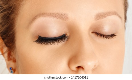 Female eyes with long false lashes, befor and after change. Eyelash extensions procedure