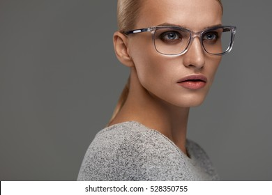 Female Eyewear. Attractive Blonde Girl With Natural Face Makeup In Transparent Glasses Frame. Beautiful Young Woman Wearing Stylish Fashion Optical Eye Glasses On Grey Background. High Resolution