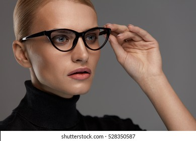 Female Eyewear Style. Portrait Of Beautiful Sexy Young Woman Wearing Fashion Eyeglasses On Grey Background. Closeup Of Attractive Blonde Model Girl In Black Optical Glasses Frame. High Resolution