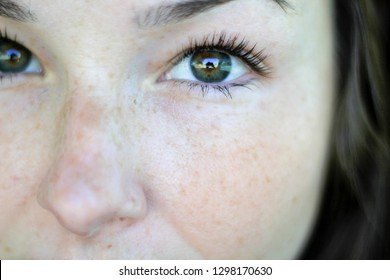 Female Face Closeup. Youthful looking caucasian girl with green eyes, freckles, long eyelashes, and wavy brown / brunette hair.