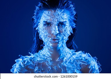 Female face covered with a lot small pieces of glass or ice. Realistic visual effects made of silicone gel.