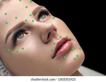 Female face marked with green dots on the main facial spots for beauty injections. Caucasian woman in spa salon, selected focus. Rejuvenation procedure, beautician, mesotherapy, pattern, skin care