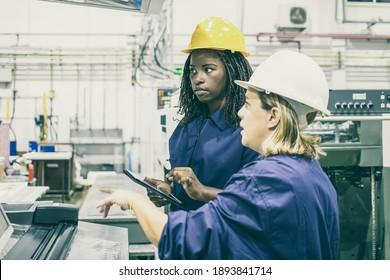 Weibliche Fabrikangestellte, die zusammen Maschinen auf dem Pflanzenboden bedienen, Tablet benutzen und Monitore über dem Bedienfeld betrachten. Seitenansicht. Herstellungsverfahren oder Maschinenkonzept