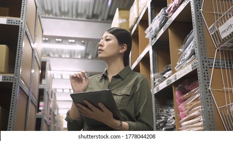 Female factory worker organizing goods arrival. Warehouse inventory manager checking distribution storage area. Cardboard boxes and smiling woman at work with digital tablet in stockroom indoors.