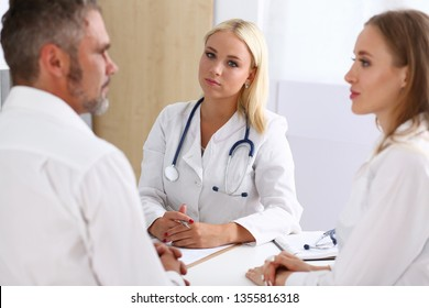 Female family doctor listen carefully young couple in office.