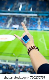 Female fan gestures hand during cheering on soccer game against green grass of stadium