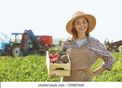 Female farmer holding wooden box with vegetables in field
