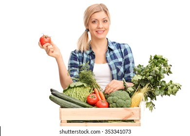 Female farmer standing behind a crate full of fresh vegetables and holding a single tomato isolated on white background