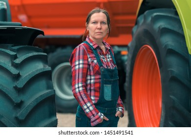 Female farmer and tractor. Woman doing men's job concept. Female farm worker posing in front of agricultural machinery.
