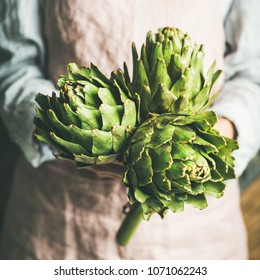 Female farmer wearing pastel linen apron and shirt holding fresh artichokes in her hands, selective focus, square crop. Organic produce or local market concept