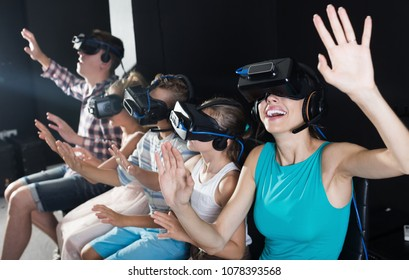 Female is fascinated by watching the video with family in the room of virtual reality