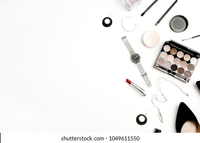 Female fashion accessories and cosmetics flatlay. Hat, shoes, palette, lipstick, watches, powder on white background. Flat lay, top view.