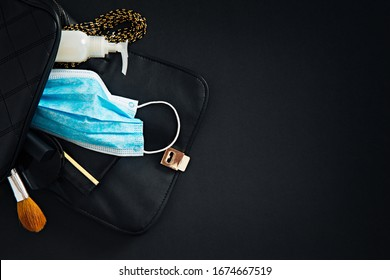 Female fashion accessories inside black leather purse, with protective breathing mask and hand sanitizer.