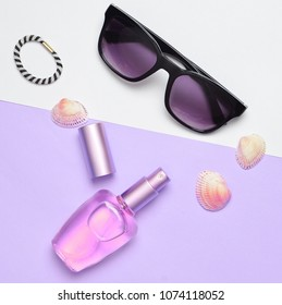 Female fashion accessories on a purple white pastel background. Sunglasses, perfume bottle, shells. Summer beach accessories. Top view, minimalist trend, copy space, flat lay.
