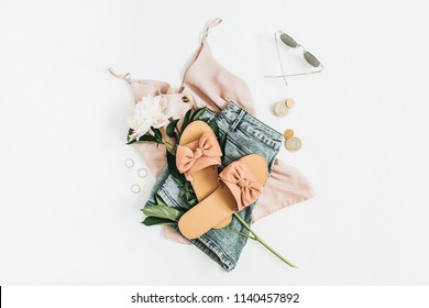 Female fashion background with white peony flower, slippers, sunglasses, earrings, shorts, t-shirt. Flat lay, top view.