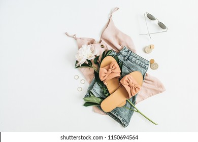Female fashion background with white peony flower, slippers, sunglasses, earrings, shorts, t-shirt. Flat lay, top view beauty or fashion blog concept.