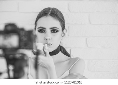 Female fashion, beauty and advertisement concept. Woman or girl with smokey eyes eat apple and look in camera on white brick wall. Nutrition, healthy lifestyle, health, diet concept.