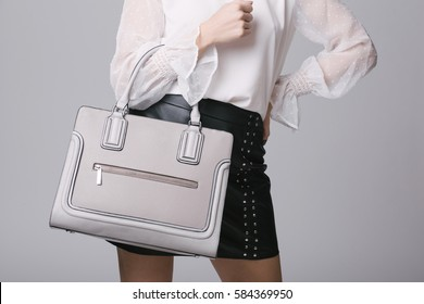 Female fashion. Closeup girl shapely figure wearing black skirt, white shirt and leather bag handbag. Studio shot
