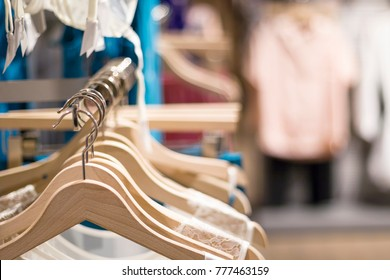 Female fashion clothing, lingerie, pajamas on hangers at the showroom, shop, store, boutique or shopping mall. Pastel colors. Close up with blurred background