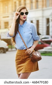 Female fashion concept. Outdoor portrait of young beautiful confident lady walking on the street. Model wearing stylish clothes and sunglasses. Girl looking aside. Sunny day. City lifestyle. Waist up