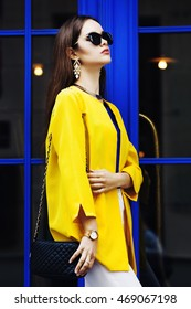 Female fashion concept. Outdoor portrait of a young beautiful confident fashionable woman posing near blue door. Model wearing stylish clothes. Girl looking up. Sunny day. City lifestyle. Waist up