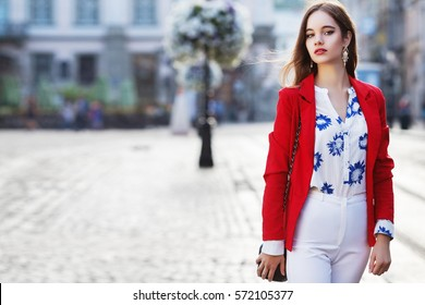 Female fashion concept. Outdoor waist up portrait of young beautiful woman posing on old street. Model wearing stylish clothes, looking at camera. Sunny day. City lifestyle. Copy, empty space for text