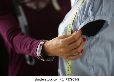 Female fashion designer arm making new dress closeup