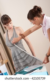 Female fashion designer measuring model for fitting gray dress, taking measurement