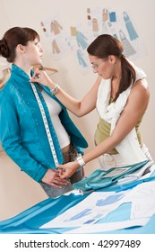 Female fashion designer measuring turquoise jacket on model, taking measurements