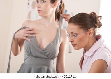 Female fashion designer pinning gray dress on model