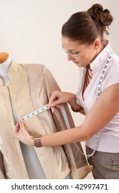 Female fashion designer taking measurement of jacket at studio