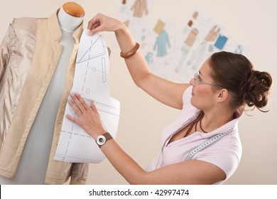 Female fashion designer working with pattern cutting at studio