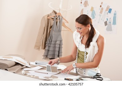 Female fashion designer working with sketches at studio and choosing cloth