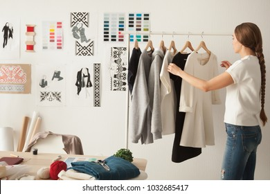 Female fashion designer works on new womenswear collection for clients in cozy workshop studio, dressmaker, tailor or needlewoman standing near clothing rack with fashionable stylish handmade clothes