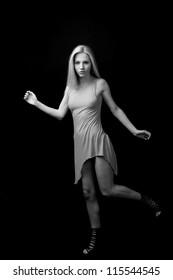 female fashion model posing at black background full length