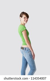 female fashion model posing at light grey background wearing blue jeans and green top