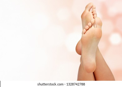 Female feet against an abstract background with circles and copyspace