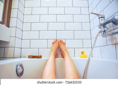 Female feet in bathroom first-person view. the girl lifted her legs up while enjoying bathing in the bathroom.