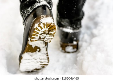 Female feet in black boots, winter walking in snow