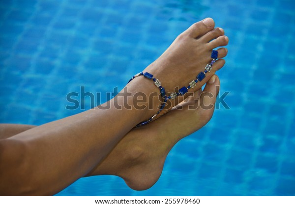 Female feet with bracelet on ankle above the pool