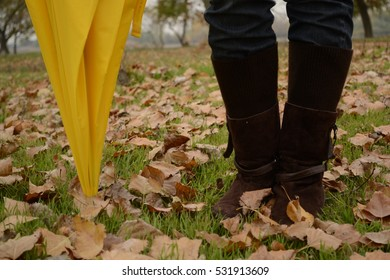 Female feet in brown shoes in the green grass and fallen autumn leaves. Yellow umbrella.