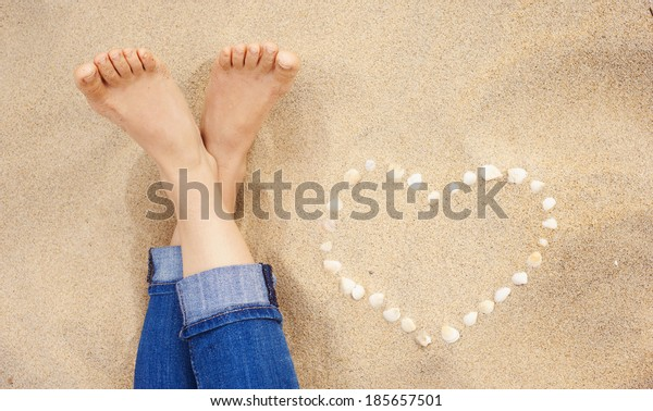 Female feet closeup of woman standing at the sandy beach next to the shell heart
