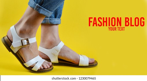 Female feet dressed in jeans and shod in sandals stepping isolated on yellow background. Fashion blog. Women's fashion. Women's summer footwear. Copy space