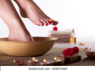 Female feet with drops of water, spa bowl, towels, flowers, candles, sea salt and bottle with essential oil on white background. Foot spa concept.